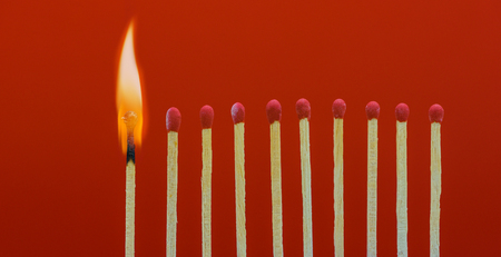 Burning matchsticks setting fire to its neighbors, a metaphor for ideas and inspiration Stock Photo