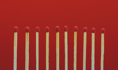 pile of matchsticks arrange in a row on a red background.