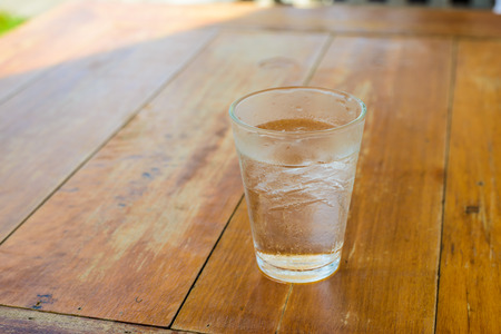 Cold drinking water and ice in the glass on wooden table