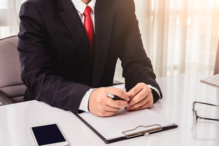 autograph: Close-up of male hands with pen over document on office desk Stock Photo
