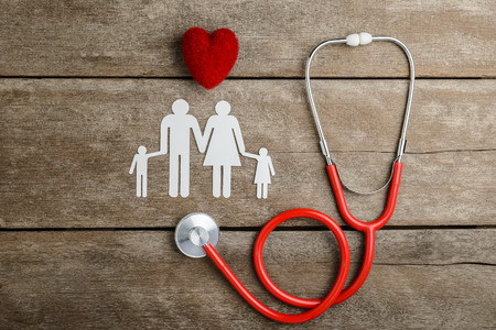 Red heart, stethoscope and paper chain family on wooden table, Health Insurance Concepts Standard-Bild