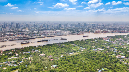 Aerial View of Bangkok skyline and view of Chao Phraya River View from green zone in Bang Krachao, Phra Pradaeng, Samut Prakan Province. Harbors and large cargo ships of Bangkok
