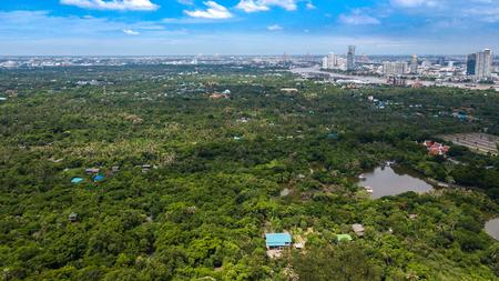 Aerial View of Bangkok skyline and view of Chao Phraya River View from green zone in Bang Krachao, Phra Pradaeng, Samut Prakan Province. Harbors and large cargo ships of Bangkok