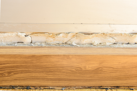 Floor moldings and paint color swelling on old white wall. rust Damage from construction is not standard. house wall or background decoration, vintage and retro concept