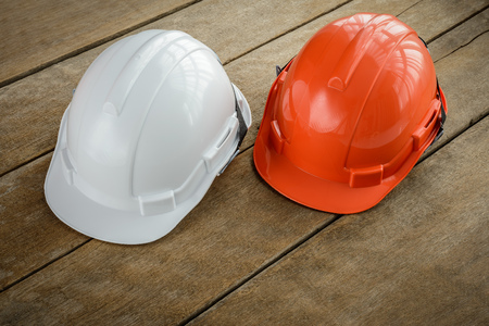 construction project: white, orange hard safety helmet construction hat for safety project of workman as engineer or worker, Engineering Construction worker equipment, on wooden floor