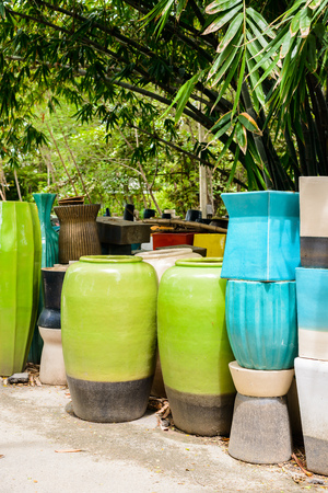 antique factory: multicolored ceramic bowls, Colorful pots and cups or vases handcrafted. Placement for gardening and walkways arrangement