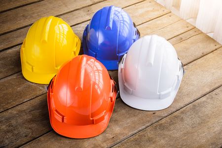 White, blue, orange, yellow hard safety helmet construction hat for safety project of workman as engineer or worker, Engineering Construction worker equipment, on wooden floor