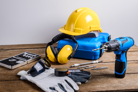 Drill and set of drill,tools,carpenter and safety, Protection Equipment on wooden table background Stock Photo