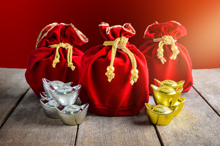 Chinese New Year Red fabric bag, ang pow with Chinese money of luck and Shoe-shaped gold ingot (Yuan Bao with Chinese character Fu means fortune), Traditional chinese (Foreign text means blessing)