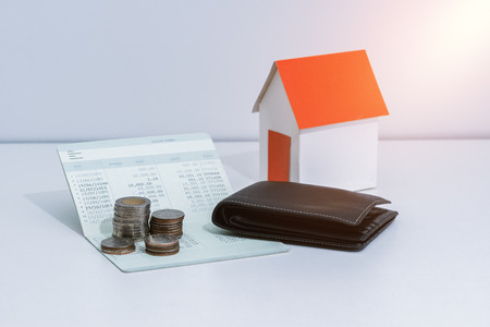 saving account passbook or financial statement, paper house model, and coins on office desk table. Business, finance, property ladder or mortgage loan concept
