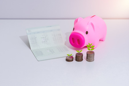 stack of coins with piggy bank and account book bank on the table in saving, banking and finance concept
