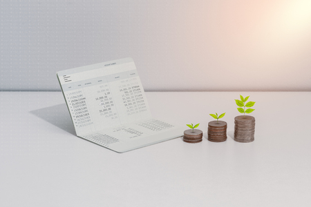 stack of coins, Little tree and account book bank on the table in saving, banking and finance concept