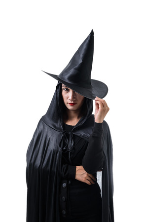 Portrait of woman in black Scary witch halloween costume standing Her hand caught on the hat isolated on white background Stockfoto