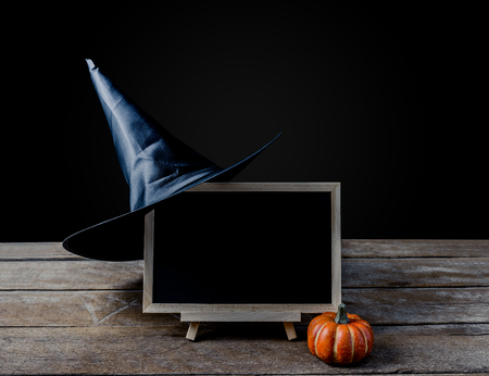 Halloween background. chalkboard on the stand, Witch hat with Halloween Pumpkins on wooden floor and black background