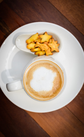 Cup of coffee hot latte on wooden table with little cookie in coffee shop. top view and copy space