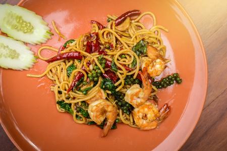 Stir-fried Spicy Spaghetti Seafood Thai food Style (Spaghetti Pad Kee Mao) in Orange Dish on wooden table