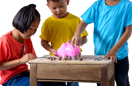 Group of asian children are helping putting coins into piggy bank isolated on white background with clipping path. Education Savings concepts