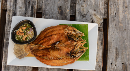 Deep Fried Snapper topped with Sweet Fish Sauce on wooden table. Top view 写真素材