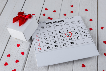 Calendar page with red hand written heart highlight on February 14 of Saint Valentines day with red Heart shape, Gift box on white wooden table 版權商用圖片