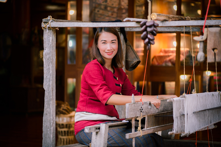 Women in thai dress are weaving with ancient weaving machines