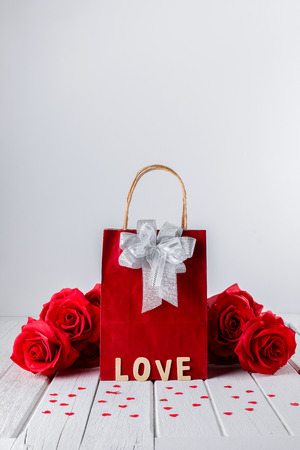 Valentines background with red rose, Heart shape, Gift bag, Wooden letters word LOVE on white wooden table