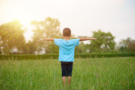 Asian Kid standing and stretch the arms or extend arms in the grass fields in sunset time