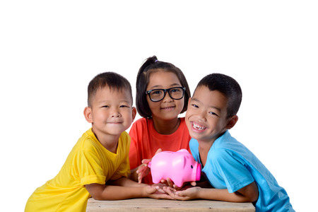Group of asian children have fun with piggy bank isolated on white background with clipping path. Education Savings concepts Stockfoto