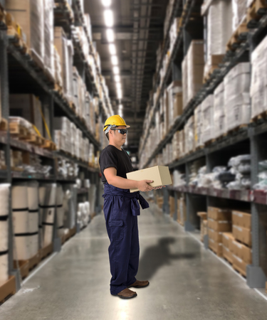 Worker in Mechanic Jumpsuit with holding parcel boxes with Blurred the background of the warehouse Stock Photo