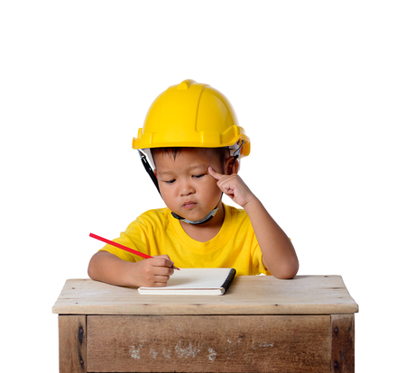 Asian children wearing safety helmet and thinking planer with pencil, note book isolated on white background with clipping path. Kids and education concept