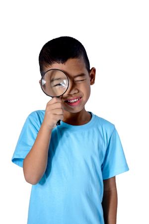 Glückliches Kind, das mit der Lupe auf weißem Hintergrund mit Freistellungspfaden erforscht