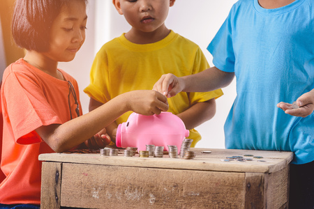Group of asian children are helping putting coins into piggy bank on white background. Education Savings concepts