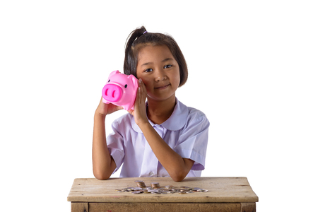 Cute asian girl in school uniform have fun with piggy bank and coins isolated on white background with clipping path. Education Savings concepts Stock Photo