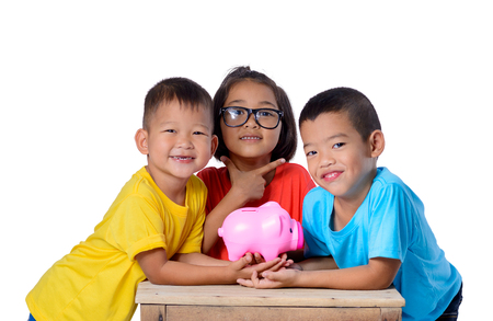 Group of asian children have fun with piggy bank isolated on white background with clipping path. Education Savings concepts Stock Photo