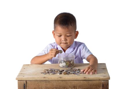 Cute asian country boy putting coins into Glass bowl isolated on white background with clipping path. Education Savings concepts Stock Photo