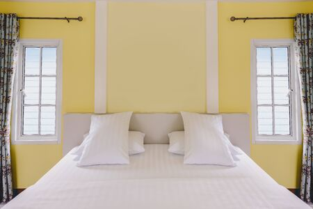 Modern yellow bedroom interior and white bedding in vintage house