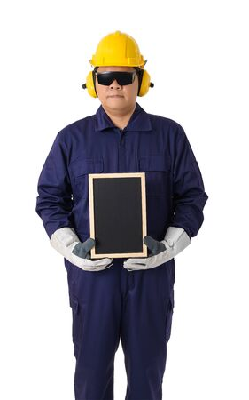 Full body portrait of a worker in Mechanic Jumpsuit with helmet, earmuffs, Protective gloves and Safety goggles holding chalkboard isolated on white background clipping path