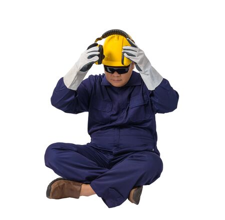 worker in Mechanic Jumpsuit with helmet, earmuffs, Protective gloves and Safety goggles is Sitting isolated on white background clipping path
