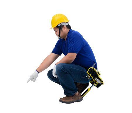 construction man workers in blue shirt with Protective gloves, helmet with tool belt sitting and Pointing finger down isolated on white backround with clipping path