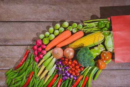 Background of fresh food tasty and healthy many vegetables come out of paper shopping bag on the wooden table. Concept of buying vegetables for health