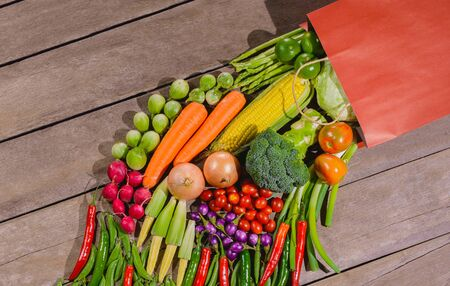 Backgroud of fresh food tasty and healthy many vegetables come out of paper shopping bag on the wooden table. Concept of buying vegetables for health Stock Photo