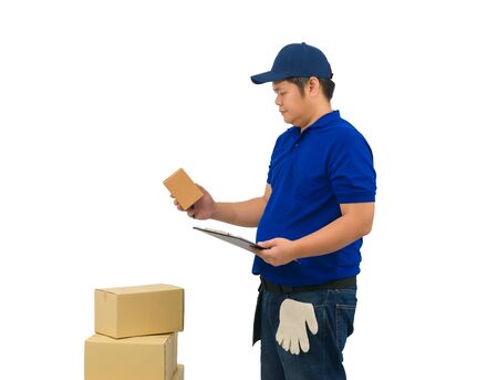 asian delivery man working in blue shirt with Waist bag for equipment hand holding parcel and clipboard for checklist or receiving form isolated white background 写真素材