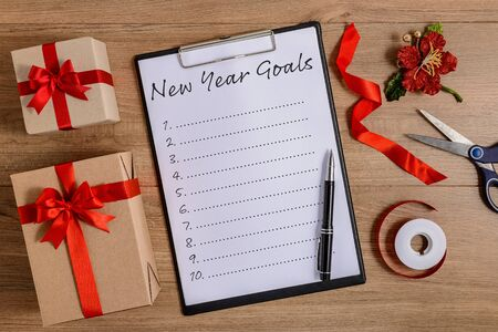New Years Goals List written on clipboard with gift box on wooden background Фото со стока