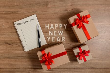 HAPPY NEW YEAR 2020 Wood New Years Goals List written on Notebook with gift box on wooden background Фото со стока