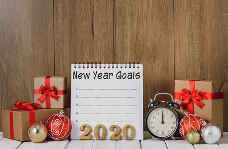 2020 wooden text and Alarm clock with Christmas ornaments, gift boxes and New Years Goals List written on Notebook over wooden background