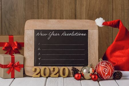 2020 wooden text and Christmas ornaments, gift boxes and New Years Resolutions List written on chalkboard over wooden background