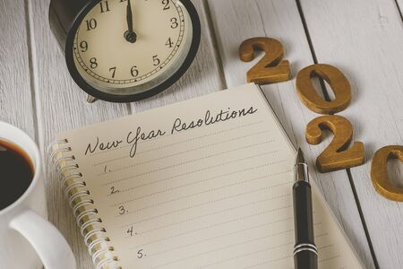 2020 wooden text and New Years Resolutions List written on Notebook with alarm clock, pen, coffee over wooden background