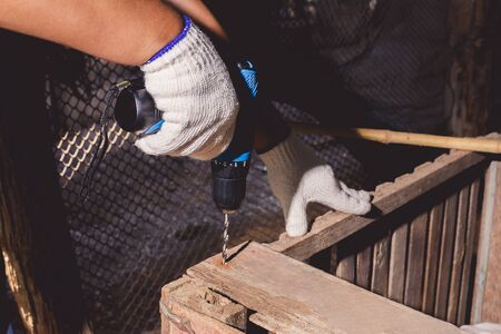construction man workers in blue shirt with Protective gloves with tool belt and working with power drill