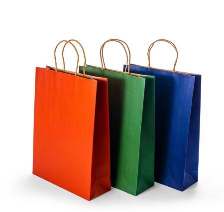 Grupo de maquetas de coloridas bolsas de papel en blanco aisladas sobre fondo blanco con trazado de recorte