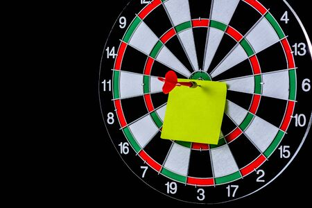 Red dart arrow hitting target center with blank sticky notes on Dart board on black background, Setting aim goal achievement concept challenging business goals, ready to achieve and Marketing concept Banque d'images