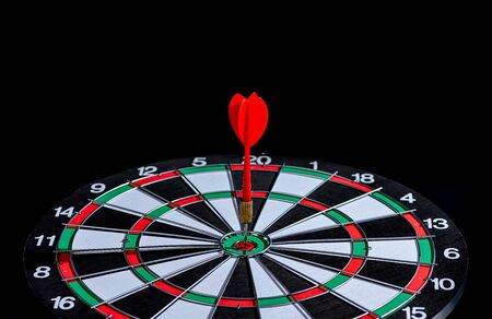 Red dart arrow hitting in the target center Dart board on Black background, Setting aim goal achievement concept challenging business goals And ready to achieve the goal and Marketing concept